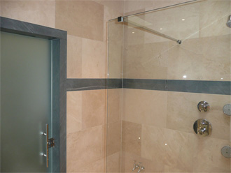 Canterbury Stone and Marble Honed Crema Marfil tiled walls. With architrave and feature line in Pietra Cardosa Limestone
