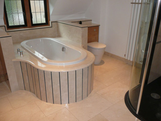 Canterbury Stone and Marble Polished Crema Marfil bath surround, cladding and tiles. With feature lines executed in Premium Black granite.