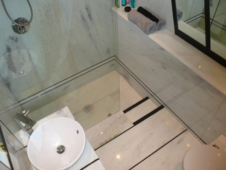 Walk in shower cladded with Verde Panama and Basalt strips.