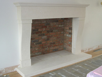 "Canterbury Stone and Marble Custom made ""Bath Stone"" fireplace with an antique reclaimed brick interior"